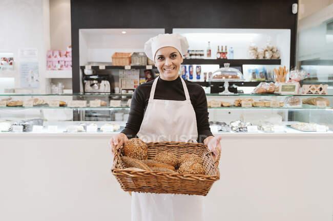 Впевнена жінка пекар тримає хліб у випалювальному кошику в пекарні. — стокове фото