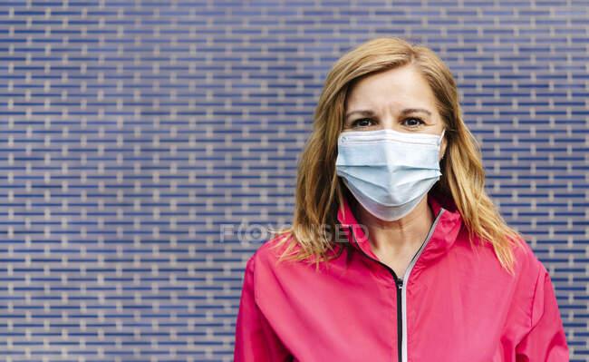Mujer con máscara quirúrgica delante de la pared azul - foto de stock