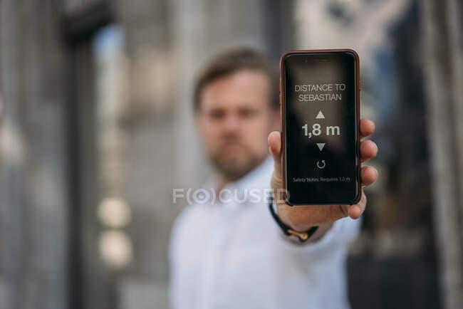 Primer plano del hombre sosteniendo el teléfono inteligente que muestra la distancia en la pantalla - foto de stock