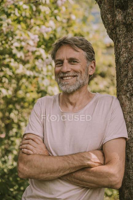 Feliz hombre maduro barbudo de pie con los brazos cruzados apoyados en el tronco del árbol en el jardín - foto de stock