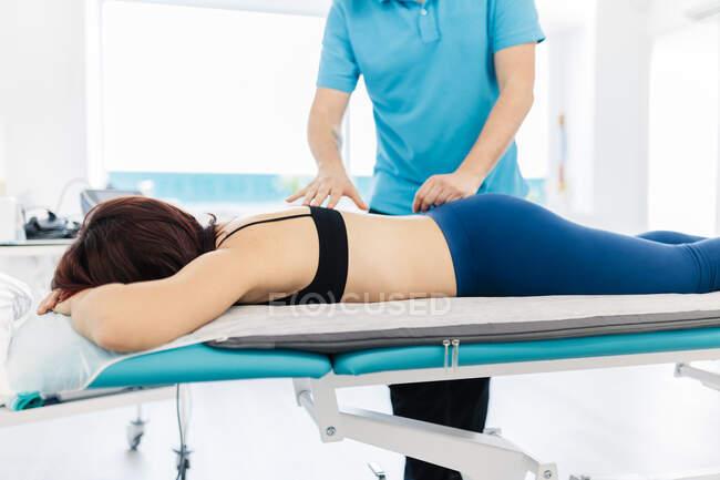 Лікар з вадами зору лікує жіночу спину в клініці. — стокове фото