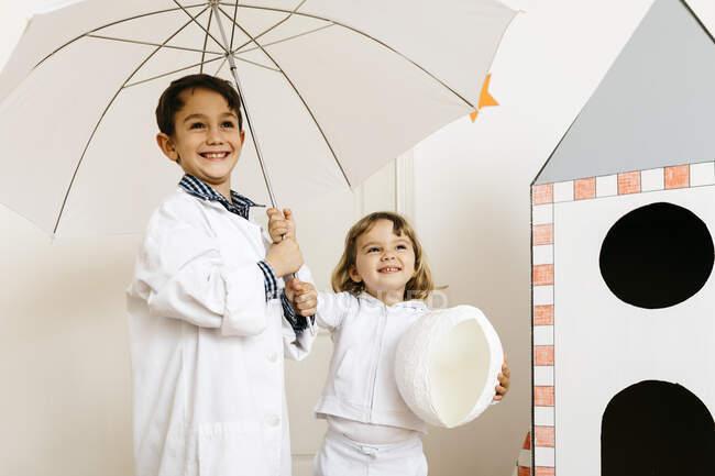 Hermanos jugando astronauta e investigador con paraguas en cohete — Stock Photo