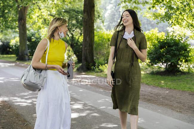Deux femmes heureuses se rencontrent dans la nature tout en portant des masques déçus — Photo de stock