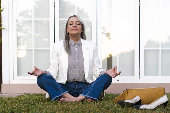 Старшая деловая женщина медитирует, сидя в позе лотоса на траве у двери офиса — стоковое фото