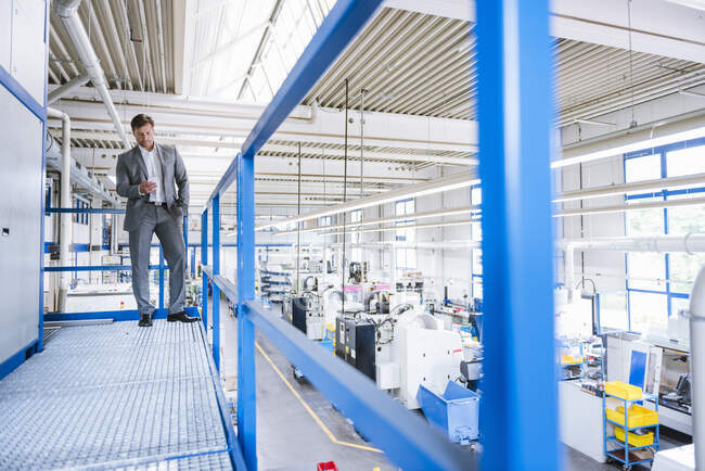 Businessman using smartphone on upper floor in a factory — Stock Photo