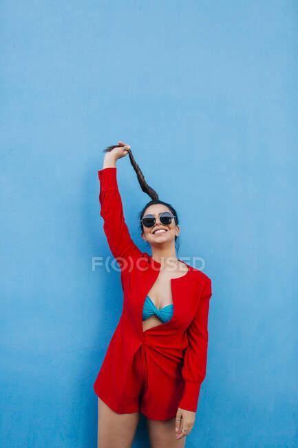 Портрет молодої жінки перед синьою стіною, що тримає свою колючку. — стокове фото