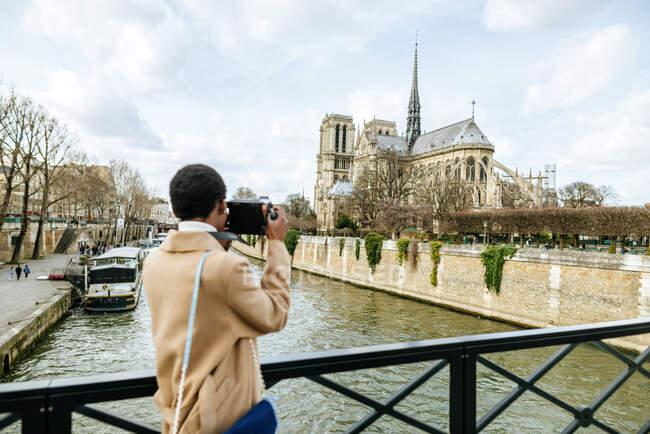 Woman photographing Notre Dame de Paris through DSLR camera against sky, Paris, France — Stock Photo
