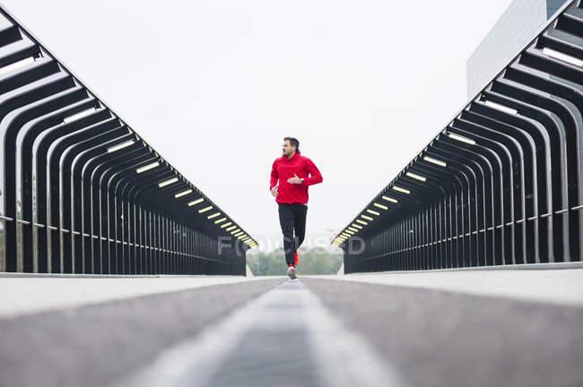 Молодой человек бежит по мосту — стоковое фото