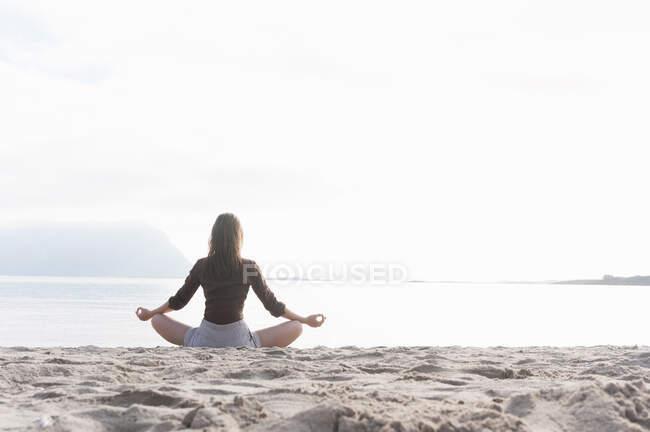 Вид сзади женщины, посредничающей на пляже, Фелиния, Италия — стоковое фото