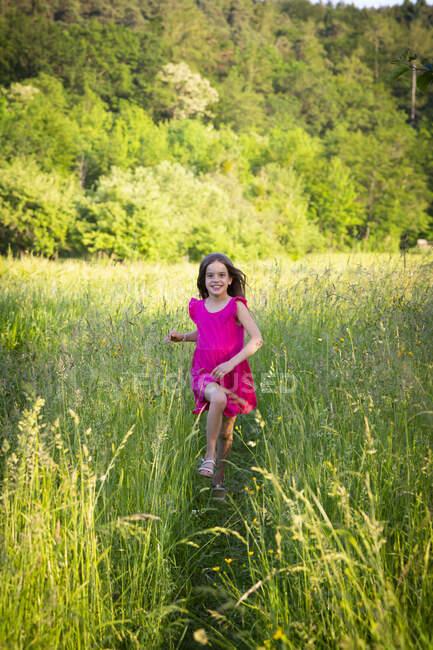 Porträt eines kleinen Mädchens, das lächelt, während es über die Wiese in Richtung Kamera läuft — Stockfoto