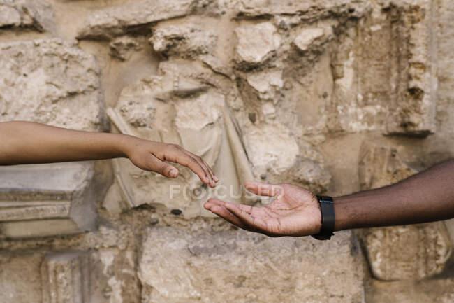 Manos de pareja que se tocan contra la pared de piedra - foto de stock