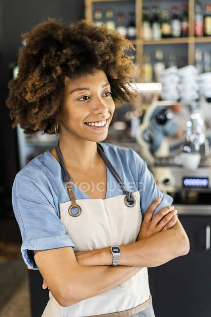 Pensativo barista hembra de pie brazos cruzados en la cafetería - foto de stock