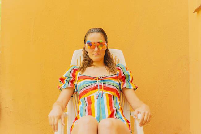 Retrato de mujer con gafas con pompones de colores que cubren sus ojos relajándose en una silla de plástico - foto de stock