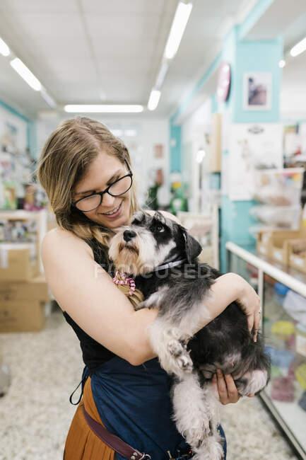 Feliz peluquero abrazando schnauzer mientras está de pie en el salón de mascotas - foto de stock
