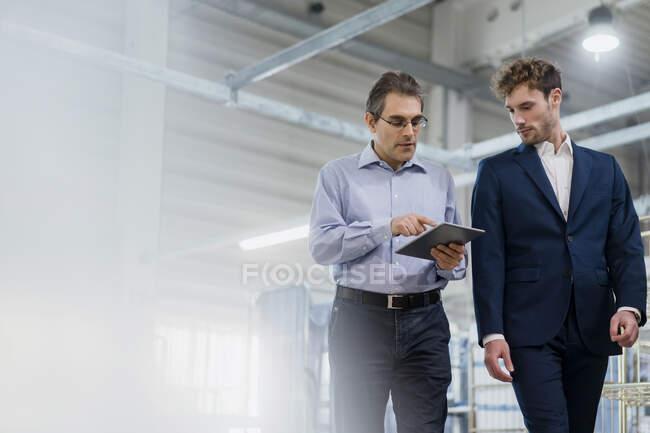 Dos hombres de negocios con tableta que tienen una reunión en una lavandería - foto de stock