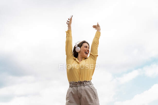 Young woman with raised arms listening to music — Stock Photo