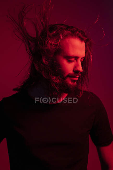 Portrait of red illuminated young man with blowing hair against red background — Stock Photo