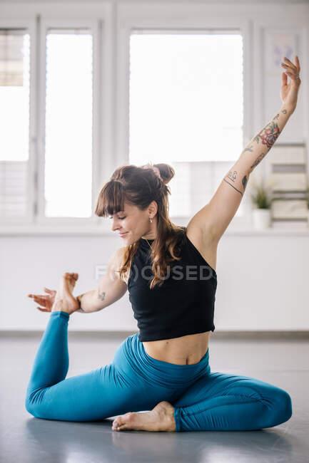 Женщина-балерина делает упражнения на растяжку на полу в танцевальной студии — стоковое фото