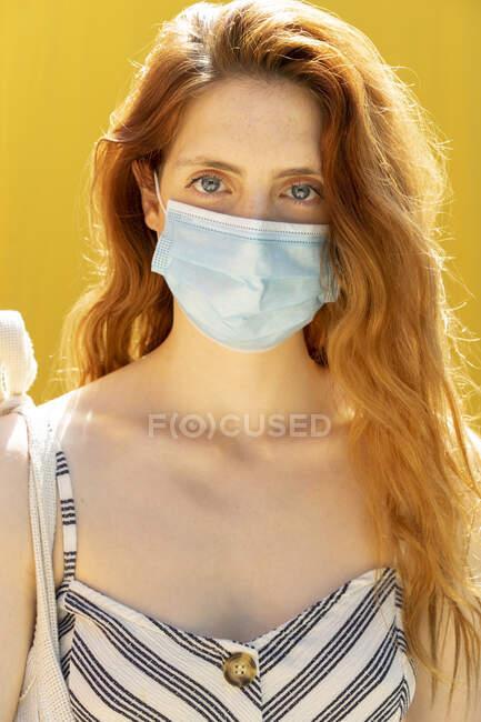 Primer plano de la joven mujer con máscara facial sobre fondo amarillo - foto de stock