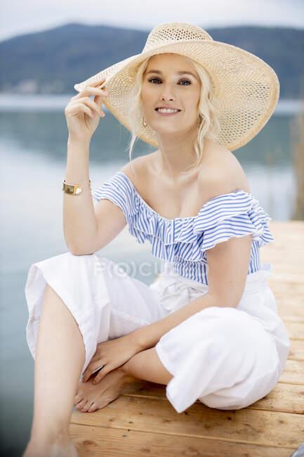 Retrato de una rubia de moda sentada en un embarcadero en Woerthersee, Austria - foto de stock