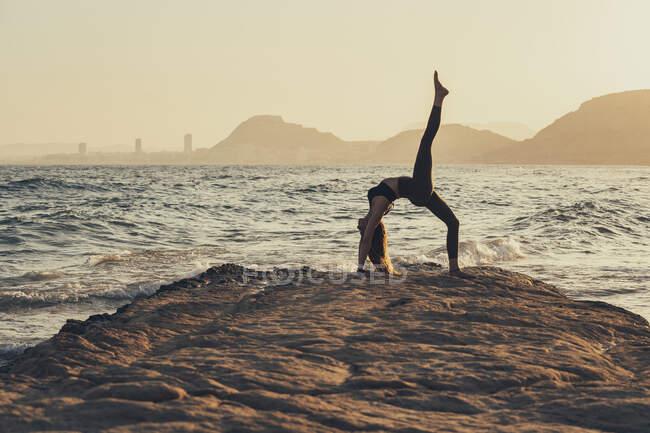 Зрелая женщина практикует йогу на скалистом пляже вечером, Урдхва Данурасана — стоковое фото