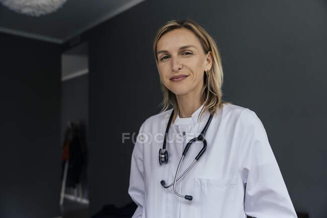 Ritratto di medico con stetoscopio su sfondo grigio — Foto stock