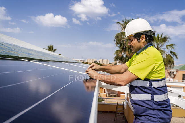 Mature technician installing solar panel on house roof against sky — Stock Photo