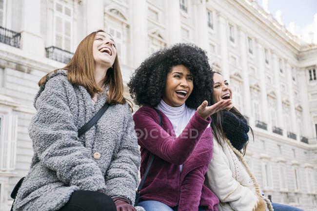 Des amies multiethniques rient en s'asseyant contre le Palais Royal de Madrid, Espagne — Photo de stock