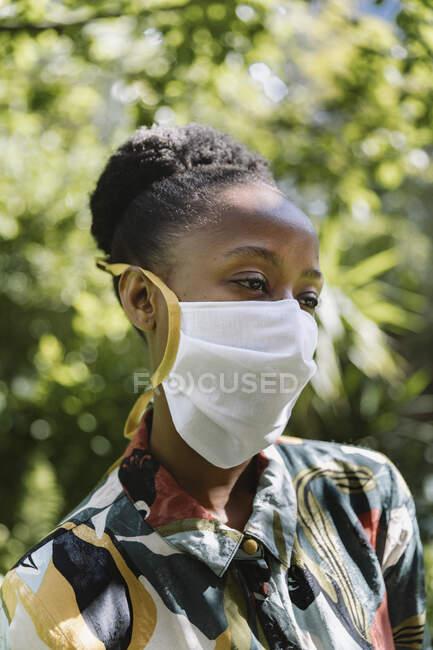 Retrato de mujer joven con máscara protectora textil blanca en el jardín - foto de stock