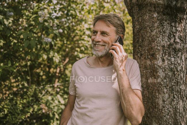 Sorrindo homem maduro falando no telefone celular enquanto se inclina na árvore no jardim — Fotografia de Stock