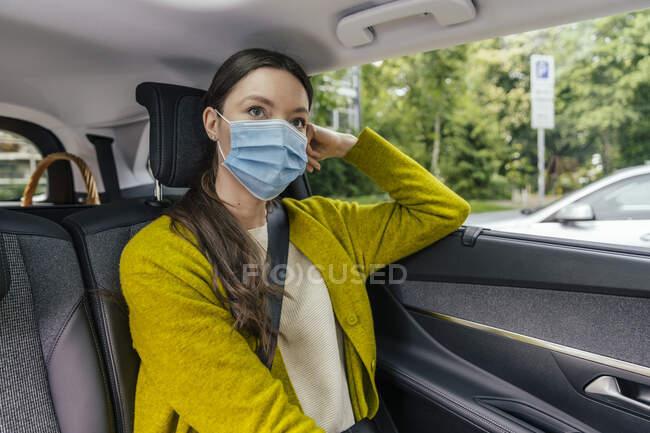 Портрет задумливої молодої жінки у захисній масці сидить на задньому сидінні. — стокове фото