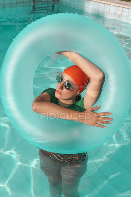 Retrato de mujer con neumático flotante en piscina - foto de stock