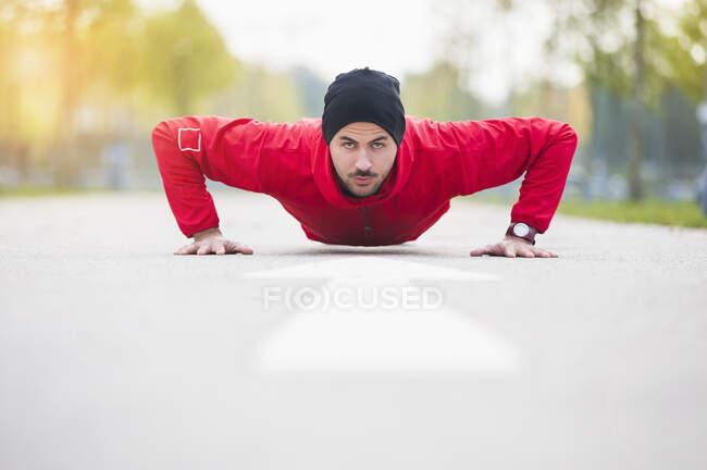 Молодой человек отжимается на дорожке — стоковое фото