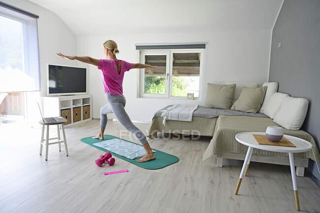 Зрелая женщина с ноутбуком практикует йогу на гимнастическом коврике в гостиной — стоковое фото