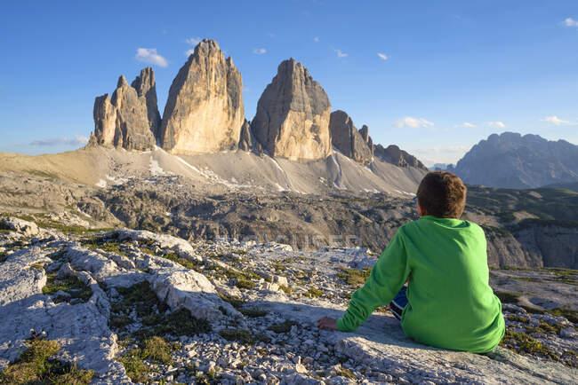 Vista trasera del niño mirando a Tre Cime Di Lavaredo contra el cielo, Veneto, Italia - foto de stock