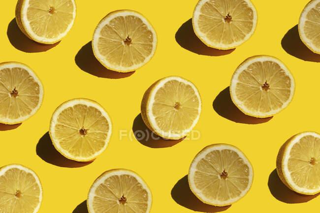 Безшовний візерунок свіжих половинок лимонів на жовтому тлі. — стокове фото