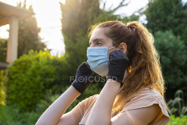 Зв'язок молодої жінки з масками і рукавичками, дивлячись подвір'я — Stock Photo