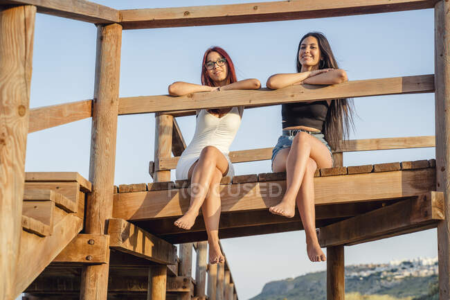 Happy teenage girls sitting on wooden pier against clear sky — Stock Photo