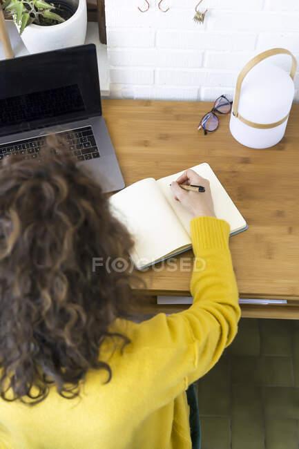 Mujer trabajando en el escritorio en la oficina en casa tomando notas - foto de stock