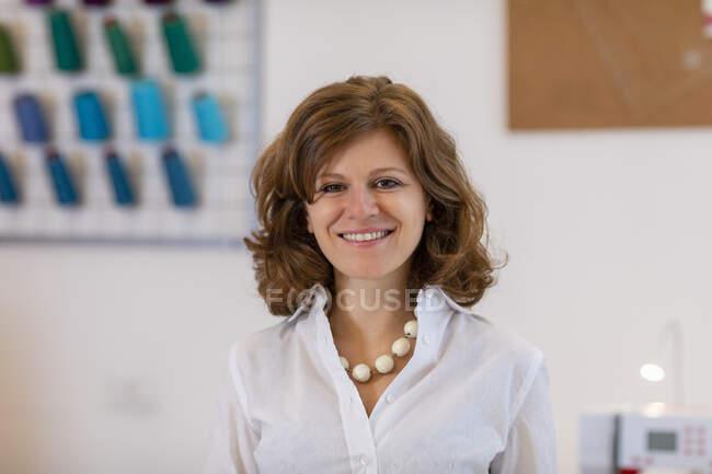Smiling female entrepreneur at fashion designing studio — Stock Photo