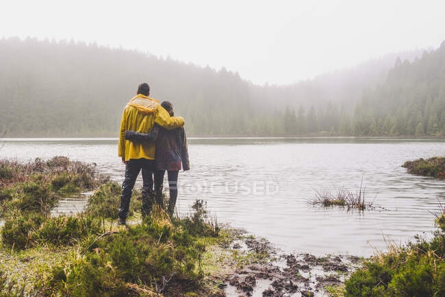 Повний задній вид молодого подружжя, що стоїть, дивлячись на річку біля лісу під час дощового сезону. — стокове фото