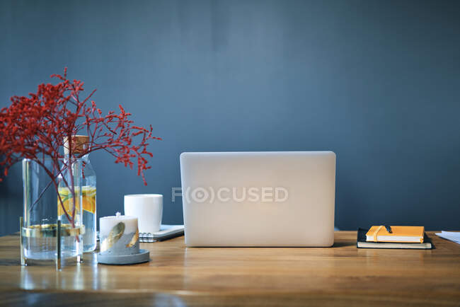 Laptop with diaries and decorations on desk against blue wall in home office — Stock Photo