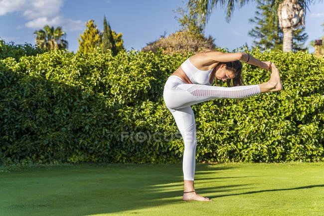 Mujer haciendo yoga en el césped bajo el sol - foto de stock