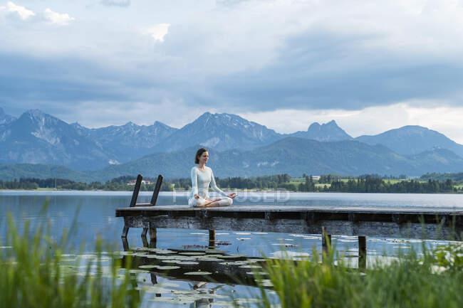 Серед дорослої жінки, яка роздумує про пристань над озером проти хмарного неба. — стокове фото