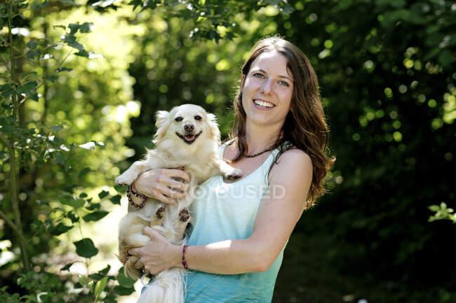 Sonriendo hermosa mujer llevando lindo perro mientras está de pie en el bosque - foto de stock