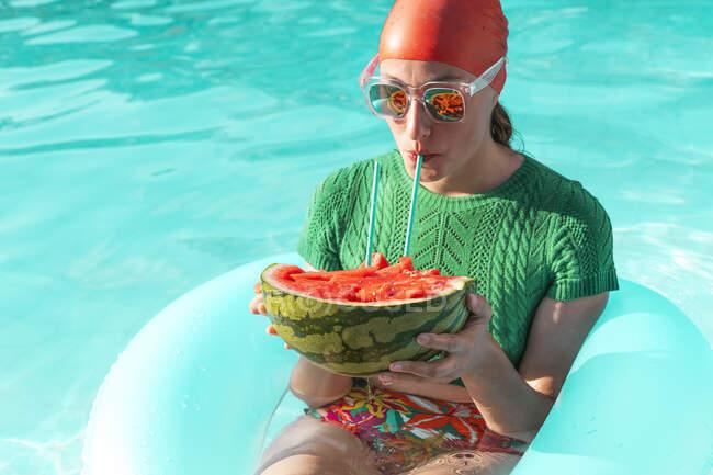 Retrato de mujer con neumático flotante y sandía en piscina - foto de stock