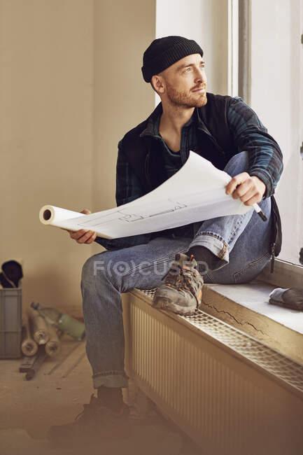 Mann renoviert Ladenlokal, sitzt auf Fensterbank, studiert Bauplan — Stockfoto