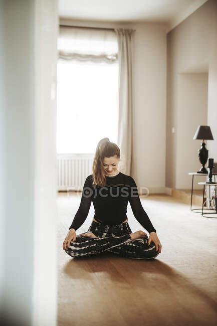 Женщина медитирует дома — стоковое фото