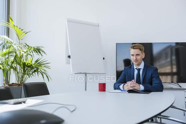 Homme d'affaires confiant assis à table dans la salle de conférence — Photo de stock