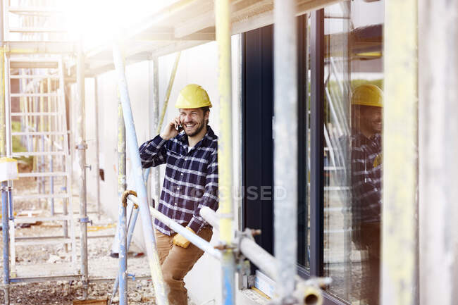 Happy worker on the phone a construction site — Stock Photo